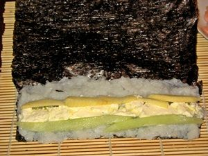на рис для ролов с креветками намазать сыр и выложить огурец с яблоком