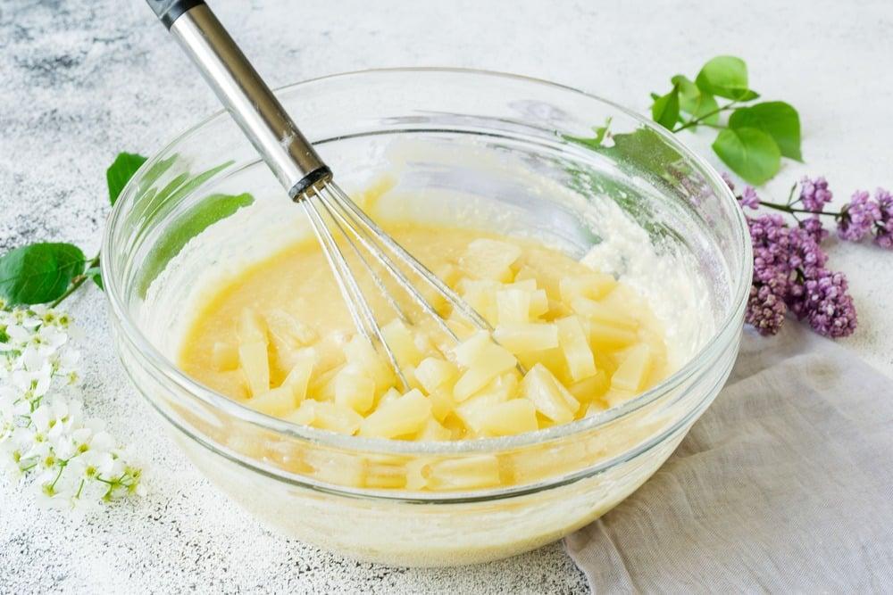 Вводим в готовое тесто консервированные ананасы