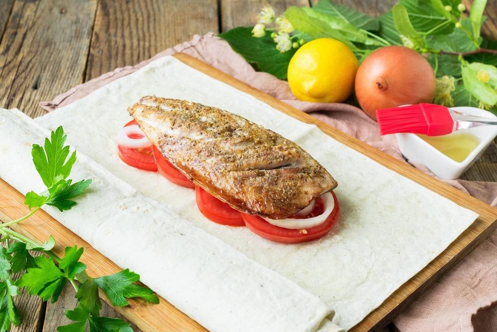 Поверх овощей выкладываем рыбу